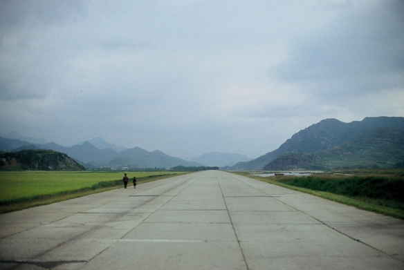 People walk at the side of a road near Wonsan, DPRK in September 2011. Image credit Frühtau via Flickr.