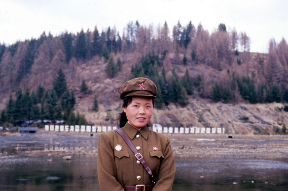 Here we visit the hot spring waterfalls in the far north of the DPRK. It's an amazing and very scenic place, where you can find relaxing nature, friendly people, and rural, quiet, and lonely villages. The guard was shy but very friendly and interested in foreign visitors. After a chat she agreed to a quick portrait of herself.